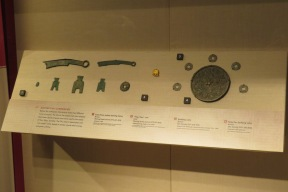 Coins from different states and time periods. The large circular object surrounded by coins is a mold for making bronze coins.