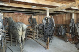 The stable room including a stuffed horse and all kinds of tack.