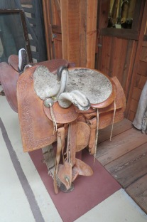 Two examples of women's side saddles. One is highly ornate with colors and much use wear. It looks almost as uncomfortable as the Army saddle. Comfort over style?!